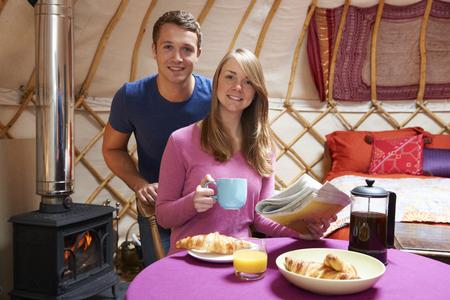 wood burner: Couple Enjoying Breakfast Camping In Traditional Yurt