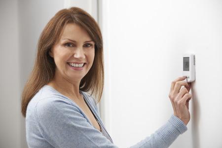 Donna sorridente di regolazione del termostato On Home Sistema di riscaldamento Archivio Fotografico