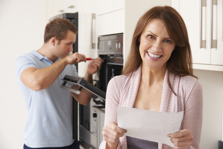 Smiling Woman With Repair Bill Stock Photo
