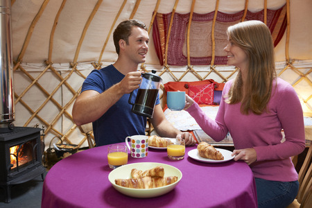 whilst: Couple Enjoying Breakfast Whilst Camping In Traditional Yurt Stock Photo