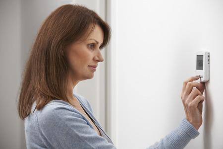 Mujer ajustando el termostato en la calefacción central Foto de archivo