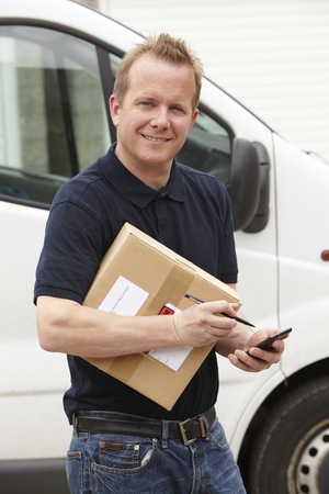 digital tablet: Courier Delivering Package Requiring Signature Stock Photo