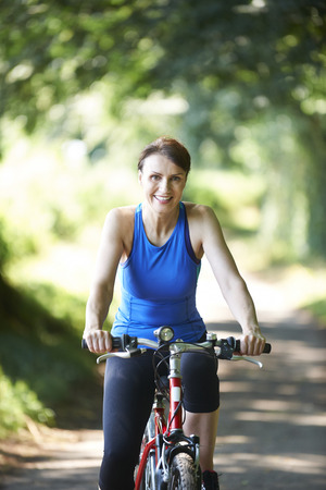 road cycling: Middle Aged Woman Cycling Along Country Lane