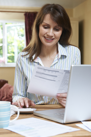 credit crunch: Smiling Middle Aged Woman Looking At Household Finances