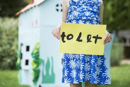 rented: Little Girl Holding To Let Sign Outside Play House