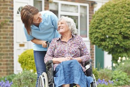 Cuidador con la mujer mayor en sillón de ruedas Foto de archivo