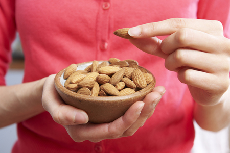 food woman: Woman Eating Healthy Snack Of Almonds Stock Photo