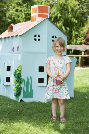 Young Girl Painting Cardboard Playhouse In Garden Stock Photo
