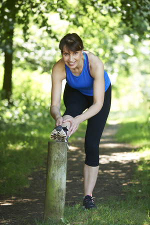 persona feliz: Middle Aged Woman Stretching On Countryside Run