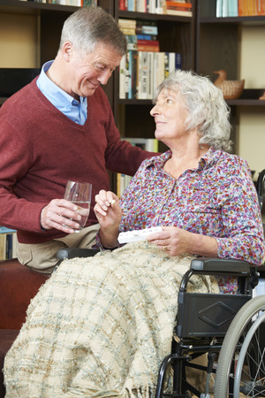 ailing: Senior Man Helping Wife In Wheelchair With Medication