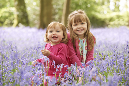 bluebell woods: Two Girls Sitting In Bluebell Woods Together