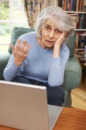 confundido: Frustrada mujer mayor Tring Para utilizar el ordenador portátil