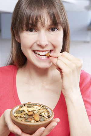 woman eating: Young Woman Eating Bowl Of Healthy Seeds Stock Photo