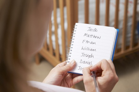 unrecognisable person: Woman Writing Possible Names For Baby Boy In Nursery
