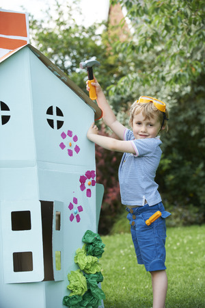 playhouse: Young Boy Pretending To Fix Cardboard Playhouse