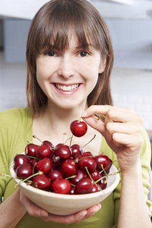 comiendo frutas: Mujer joven que come el plato de cerezas Foto de archivo