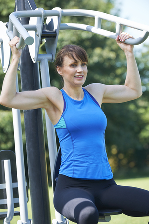 outdoor exercise: Middle Aged Woman Using Outdoor Gym Equipment Stock Photo