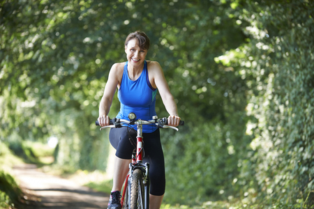 Middle Aged Woman Riding Bike Through Countryside Stock Photo