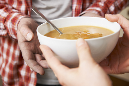 charity relief work: Homeless Man Being Handed Bowl Of Soup By Volunteer