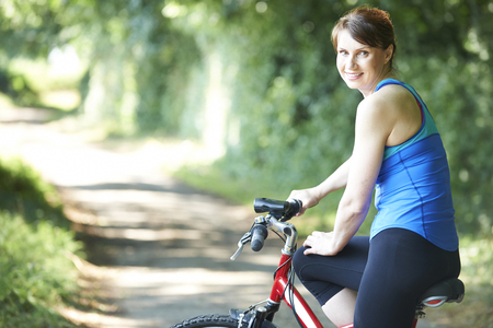 Middle Aged Woman Cycling Along Country Road