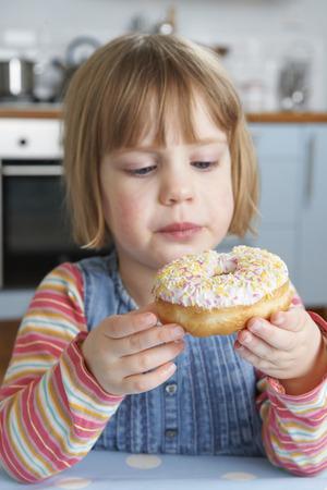 sugary: Young Girl Enjoying Eating Sugary Doughnut Stock Photo