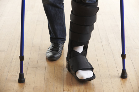 Close Up Of Man Walking With Crutches And Cast Stockfoto