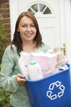 emptying: Middle Aged Woman Carrying Recycling Bin