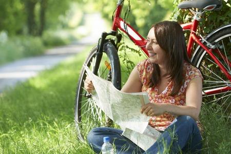 persona leyendo: Mujer en paseo del ciclo se reclinan y que mira una correspondencia Foto de archivo