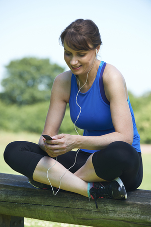 mp3 player: Middle Aged Woman Relaxing With MP3 Player After Exercise Stock Photo