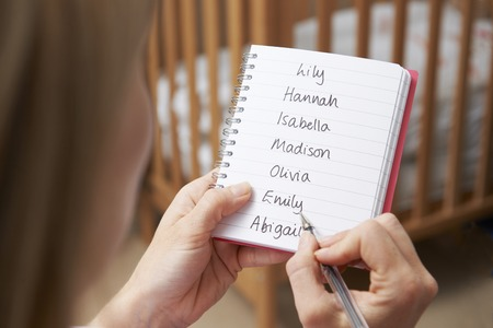 unrecognisable person: Woman Writing Possible Names For Baby Girl In Nursery