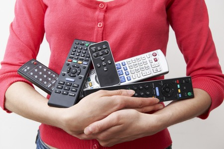 remote controls: Woman Holding Armful Of TV And Audio Remote Controls