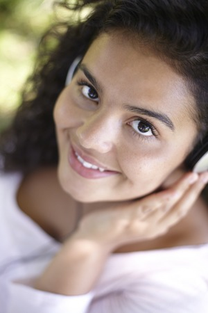 mp3 player: Pretty Woman Listening To MP3 Player Outdoors Stock Photo