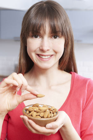 almond: Young Woman Eating Almonds From Bowl