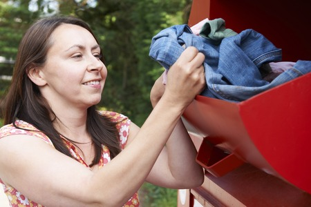 recycling center: Woman Putting Old Clothes Into Recycling Bank