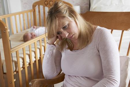 depresión: Madre en cuarto de niños que sufre de depresión posparto