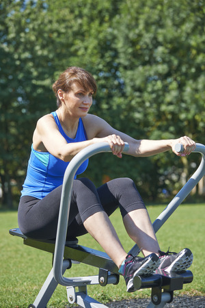 outdoor exercise: Mature Woman Exercising On Rowing Machine In Park