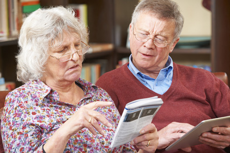 manuals: Confused Senior Couple Trying To Operate Digital Tablet