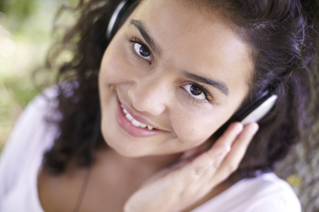 mp3 player: Young Woman Listening To MP3 Player Outdoors