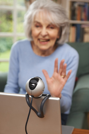 the ageing process: Senior Woman Using Webcam To Talk With Family