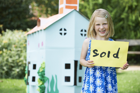 sold sign: Little Girl Holding Sold Sign Outside Cardboard Playhouse Stock Photo