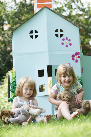 cuddly toy: Two Children Playing In Home Made Cardboard House