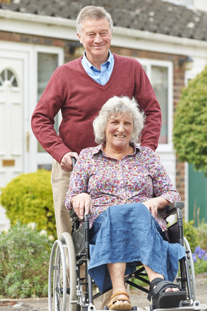 elderly woman: Senior Man Pushing Disabled Wife In Wheelchair Stock Photo