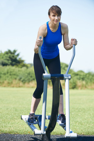 Middle Aged Woman Using Outdoor Gym Equipment Stock Photo
