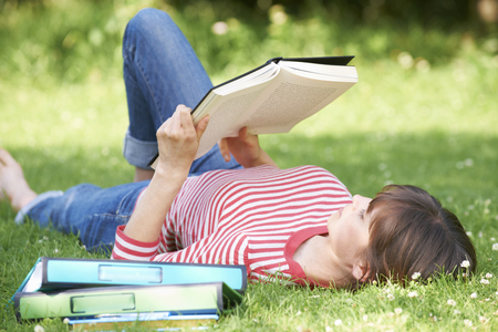 textbook: Female Student Reading Textbook In Park Stock Photo