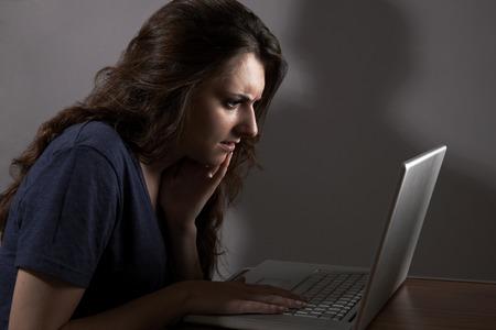 menacing: Teenage Girl Using Laptop With Menacing Shadow In Background