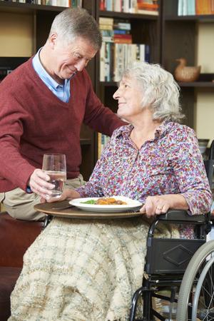paraplegic: Hombre mayor que sirve esposa en silla de ruedas Con Alimentos Foto de archivo
