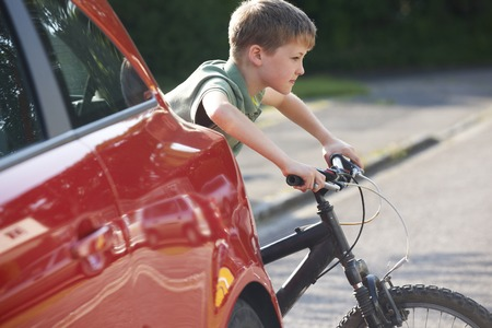 Child Riding Bike From Behind Parked Car