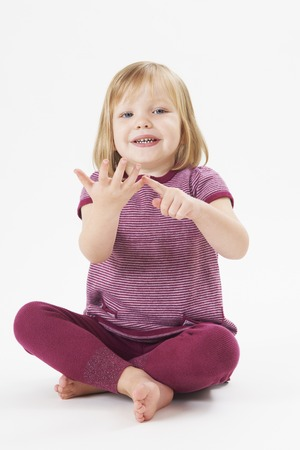 old girl: Studio Shot Of Little Girl Counting On Fingers Stock Photo