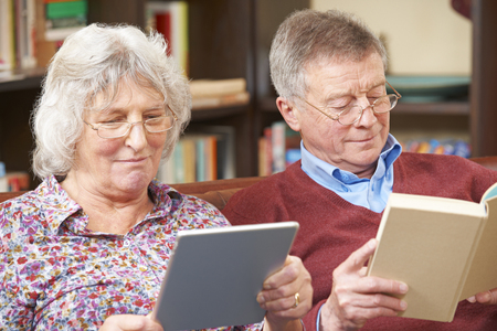 silver surfer: Senior Couple Using Digital Tablet And Reading Book