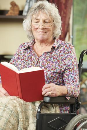 paraplegico: Mujer mayor en silla de ruedas del libro de lectura Foto de archivo
